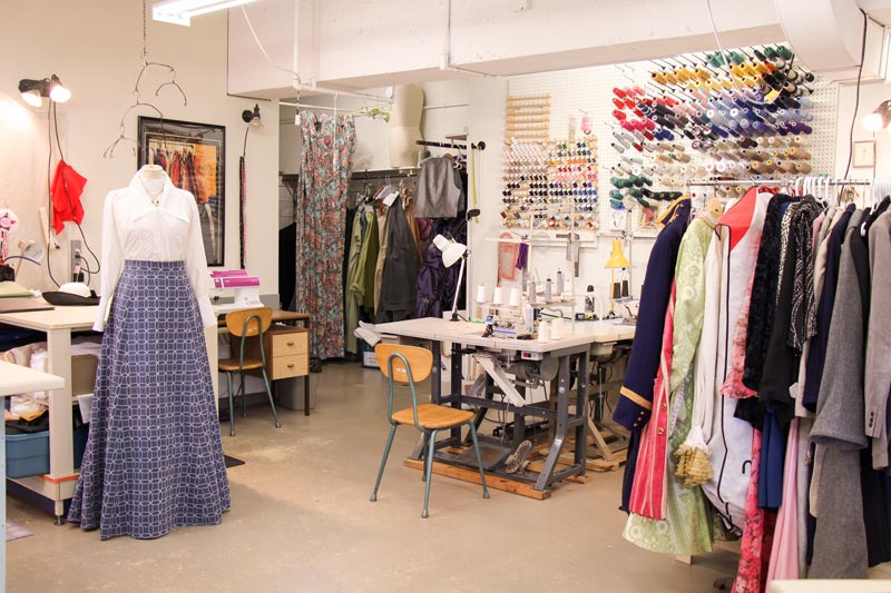 sewing station and rack of costumes