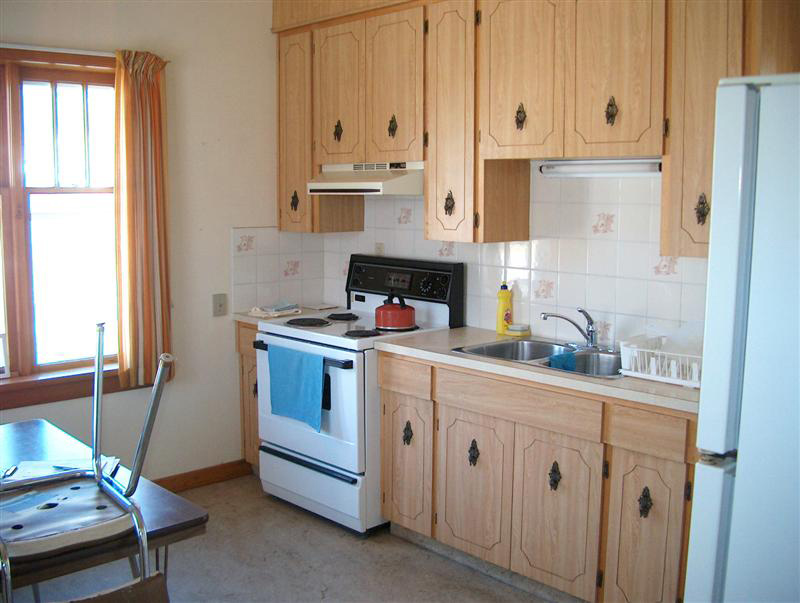 fully stocked kitchen with stove, fridge, and cupboards