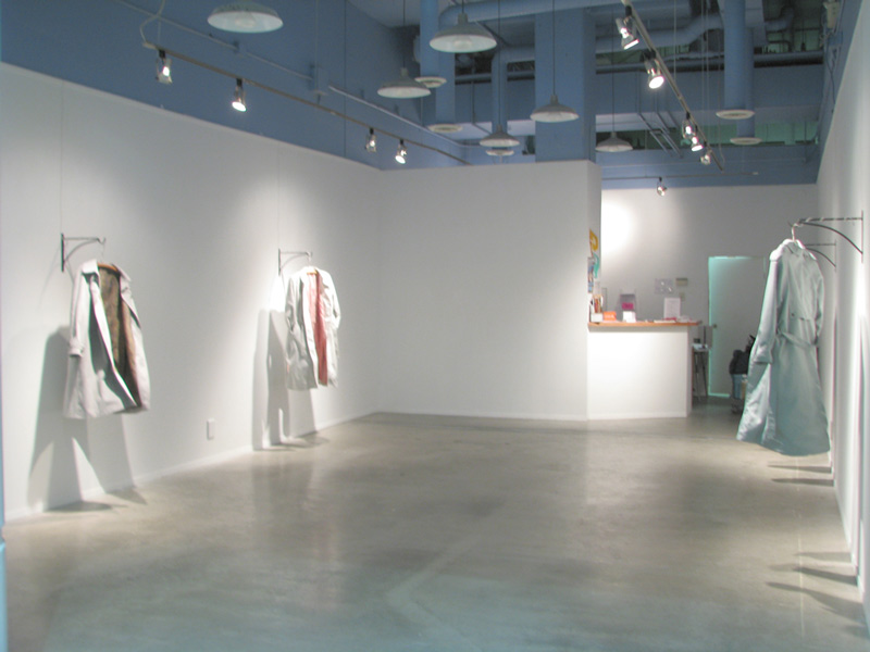 art installation with lab coats hanging from walls