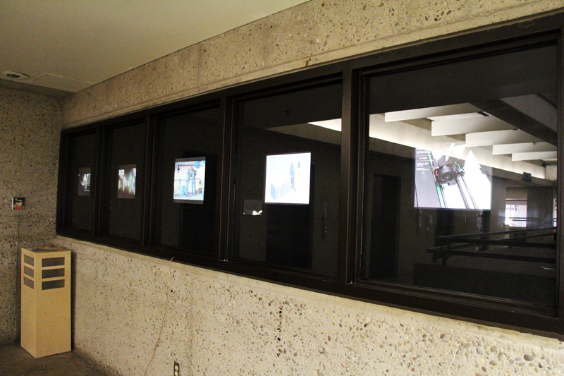 screens that face the hallway to showcase new media student work
