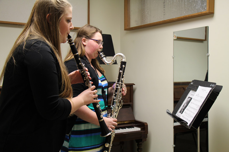 Students playing clarinet and bass clarinet in practice room
