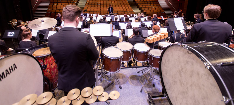 Wind orchestra performing on stage, view from percussion section