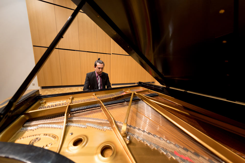 Student playing piano in the recital hall