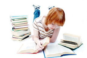 Girl reading with stack of books