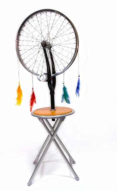 Sculpture of bicyle tire dreamweaver attached to a stool
