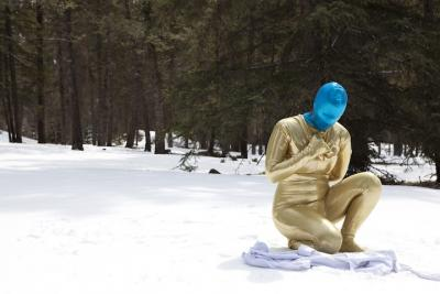 performance still of figure in gold costume in the snow