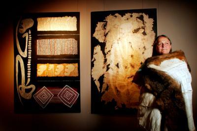 Portrait of Vicki in front of aboriginal artwork