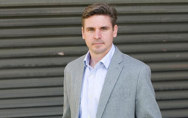 Image of Aaron Taylor standing in grey suit