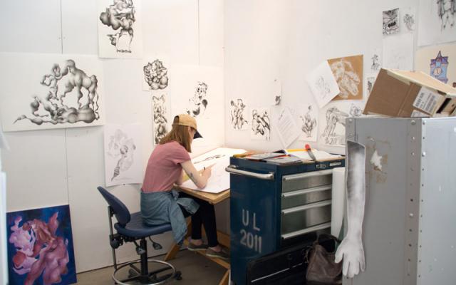 Art student sitting at individual desk