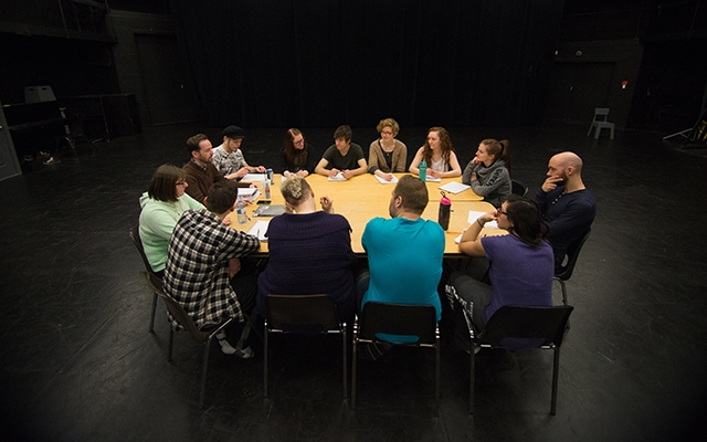 Drama students sitting around a table