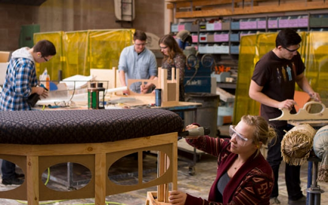 student upholstering bench in prop shop