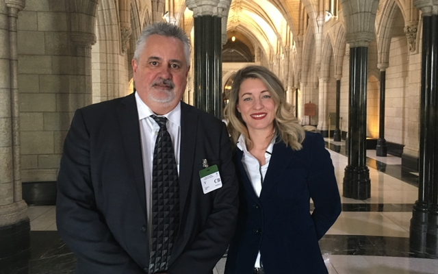 Rolf Boon standing in Parliament with Melanie Joly