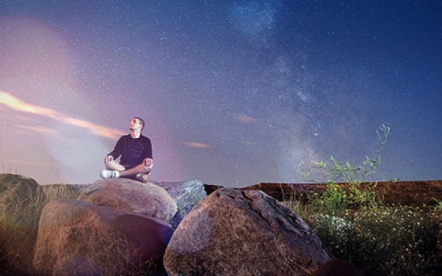 Student sitting on rock looking into night sky