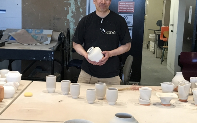 Gary Uchikura poses with his pottery