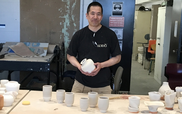 Gary Uchikura poses with his pottery