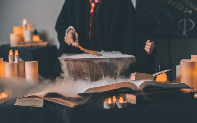 Person performing spells over a cauldron with a wand in hand.