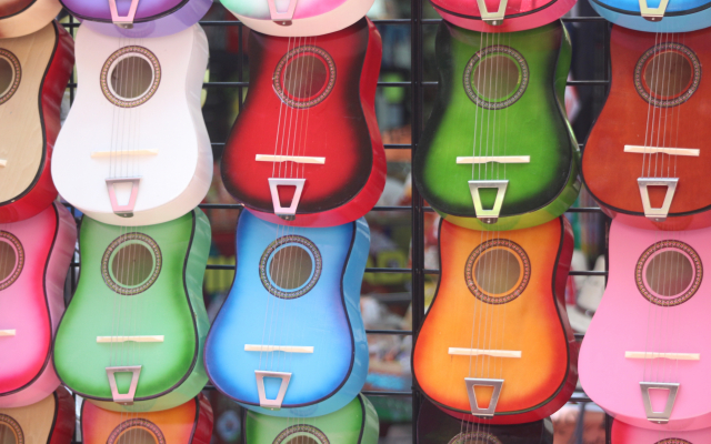 Row of colorful Ukuleles ranging from orange, blue, green and pink!