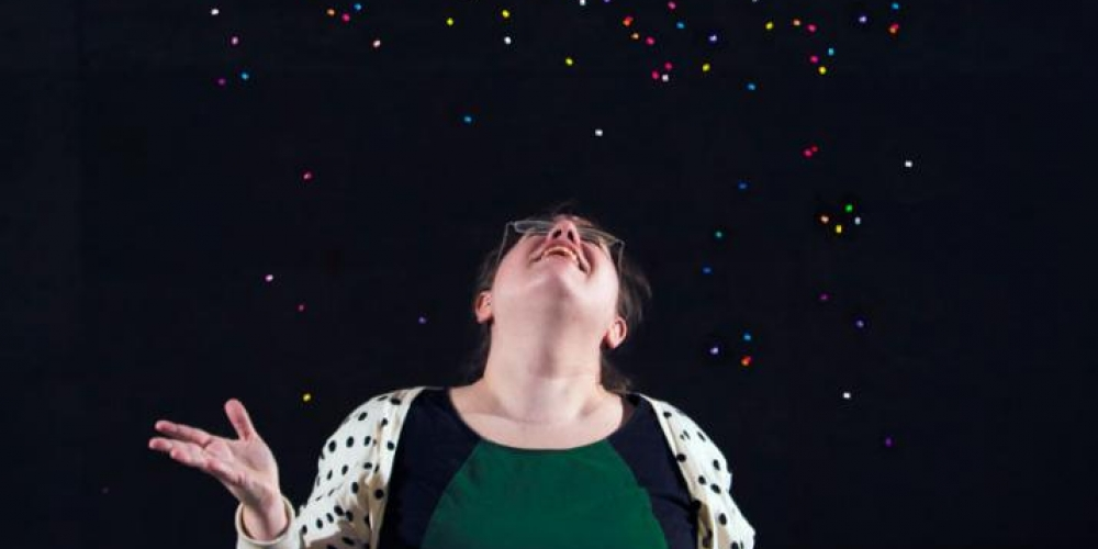 Megan Morman tossing perler beads in the air on a black background
