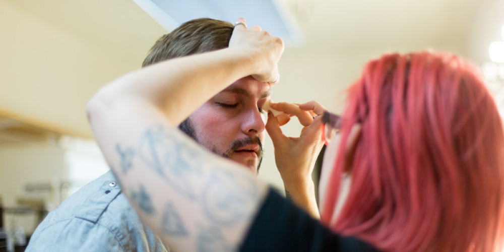 Student applying makeup to actor