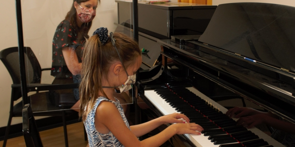 Piano lesson with masks and plexiglass divider.