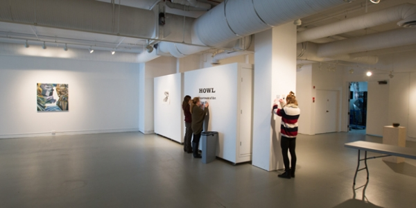 students taking down art in penny gallery