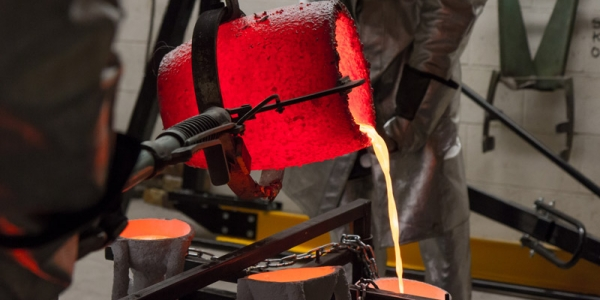 pouring liquid bronze into a cast