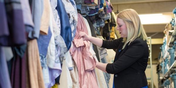 Woman ironing pink dress