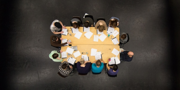 Overhead image of students in David Spinks around a table with scripts