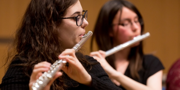 Two students playing flute in an ensemble