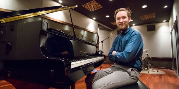 Max Hopkins sitting in front of a piano