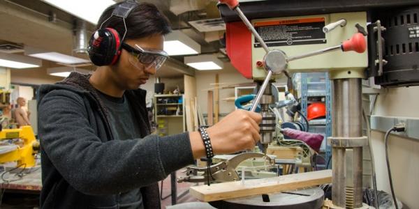 student using drill press