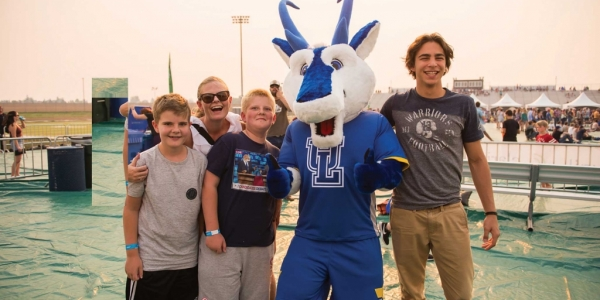 Family hanging out with Luxie, the mascot of uLethbridge
